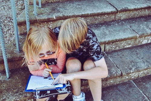two children sitting on a step doing homework