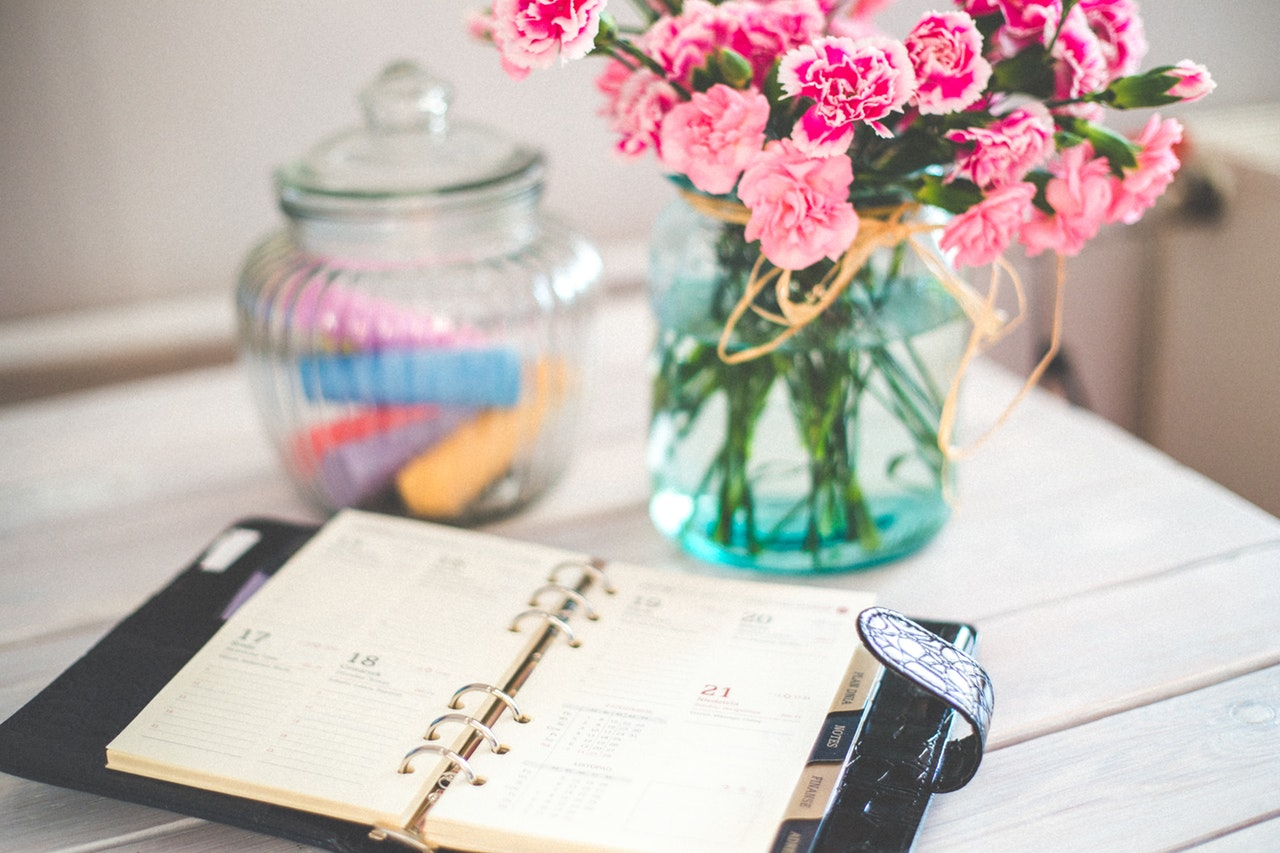 Busy Schedule filofax with vase of flowers on desk